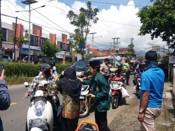 Ikatan Pelajar Putri Nadhatul Ulama (IPPNU) Kecamatan Pasirjambu membagikan masker kepada masyarakat yang melintas di Jalan Raya Pasirjambu, Rabu (5/5).