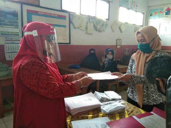 Pembagian rapot di SDN Ciranjang 1 Kecamatan Pasirjambu dilaksanakan pada ,Jumat (19/6). Nampa pada gambar seorang guru sedang membagikan buku rapot kepada orang tua sisa, dengan menarapkan standar protokol kesehatan.